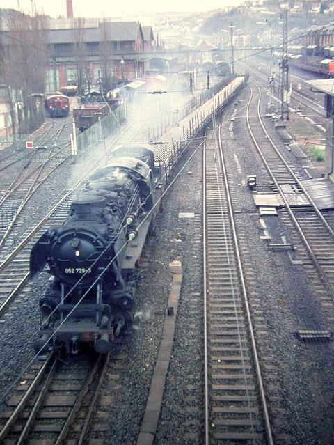 Die Einfahrt zum Aw Siegen mit der Köf-Werkslok im Hintergrund links, 052 728-3 vom Bw Betzdorf dampft mit einer Ladung Schienenprofile vorbei, Mai 1969