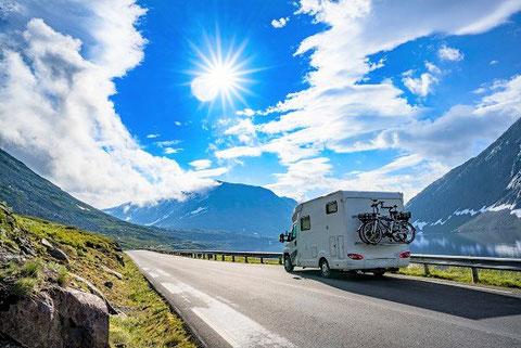 Wohnmobil mit Fahrrädern allein im Camping-Urlaub unterwegs auf der Straße zwischen Bergen, gut versichert mit dem Caravaning-Reiseschutz der ERGO