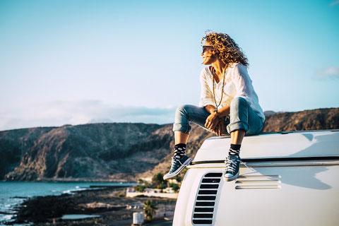 Lachendes Paar beim Camping unterwegs mit ihrem Hund, ihrem Camper, einem Campingkocher und einer CDW-Versicherung der ERGO Reiseversicherung