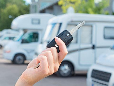 Eine Hand mit einem Schlüssel vor Campmobilen als Beispielbild für Womo Wohnmobil Camper Vermietung