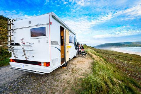 Unterwegs mit dem gemieteten Wohnwagen als Anhänger und Fahrrädern auf dem Dach in den Camping-Urlaub gut geschützt mit einer CDW-Versicherung der ERGO