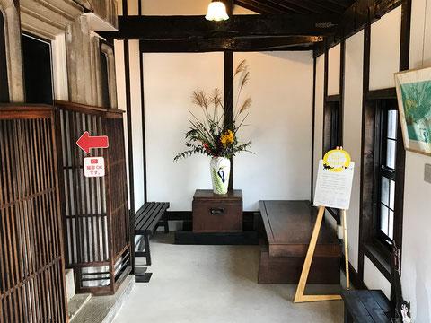 入り口を入った空間。左が入り口で分厚い扉と飾りの木枠が趣があります。 正面にあるのは火鉢です。そこに花を飾りました。