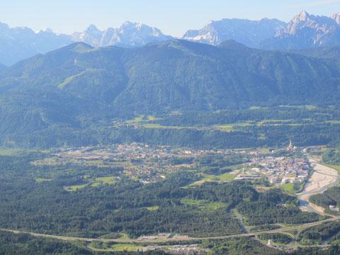 Die Marktgemeinde Arnoldstein mit dem bewaldeten Dreiländereck (1.509m) und den Julischen Alpen im Hintergrund