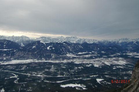 Blick hinunter ins Gailtal, im Vordergrund schlängelt sich die Gail durch die Schütt, in der Bildmitte die Marktgemeinde Arnoldstein, im Hintergrund die verschneite Nordfront der westlichen Julischen Alpen