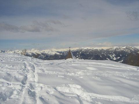 Die Kirchturmspitze vom Luschariberg, am Horizont die Hohen Tauern