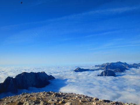 Blick vom Mangart-Gipfel Richtung Süden zum Adriatischen Meer - links die längste Gebirgswand Sloweniens, die Loška stena (Bretherwand), gerade noch aus dem Nebel ragen Rombon und Raibler Seekopf, dahinter der mächtige Karststock des Kanin