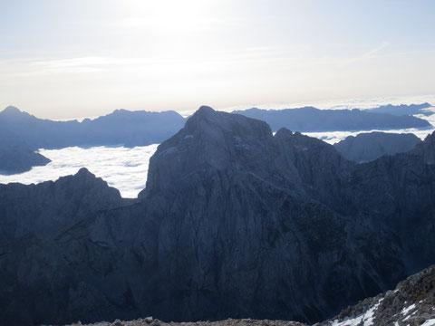 Der Jalovec vom benachbarten Mangart (2.679m) aus gesehen, beim tiefen Einschnitt vor dem Nebelmeer, dem Kotsattel (Kotovo sedlo) beginnt der Klettersteig über den Nordwestgrat auf den Gipfel des Jalovec