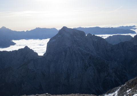 Der Jalovec vom benachbarten Mangart (2.679m) aus gesehen, beim tiefen Einschnitt vor dem Nebelmeer, dem Kotsattel (Kotovo sedlo) beginnt der Klettersteig über den Nordwestgrat
