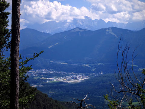Blick über Arnoldstein mit dem Dreiländereck und den wolkenverhangenen Giganten der Julischen Alpen im Hintergrund