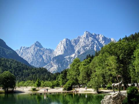 Der Jezero Jasna (Jasna-See) in Krajnska Gora mit dem bronzenen Steinbock Zlatorog und dem Razor und Prisank (Prisojnik) im Hintergrund
