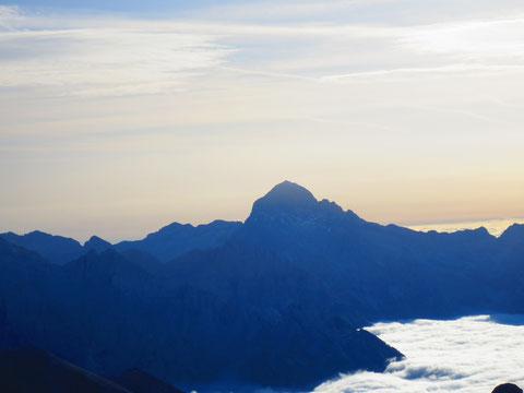 Der König der Julier, der Triglav zeigt sich in voller Pracht im Morgenlicht, links neben dem Gipfelaufbau das blinkende Blechdach der Hütte auf der Kredarica