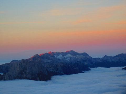 Die ersten Sonnenstrahlen streichen sanft über den mächtigen Karststock des Kanin (Monte Canin) mit seinen Gletscherresten