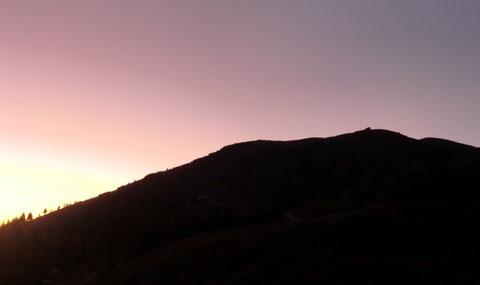 Die untergehende Abendsonne hinter dem Zehner färbt den Himmel violett