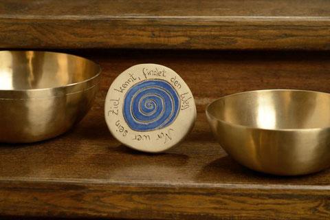 """Zwei Klangschlagen stehen auf einer Holztreppenstufe und zwischen den Schalen steht eine Tonscheibe mit dem Spruch: """"Nur wer sein Ziel kennt, findet den Weg."""""""