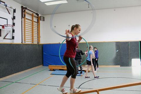 Koordinationsfähigkeit: Über einen wippenden Balken balancieren und dabei mit Reifen kreisen.