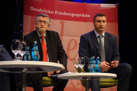 """Der Theologe Reinhold Mokrosch (links) und der Kiewer Bürgermeister Vitali Klitschko (rechts) bei den """"Osnabrücker Friedensgesprächen"""" am 26. März 2015"""