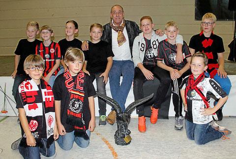 Im Anschluss an die Gesprächsrunde posierte Eintracht Präsident Peter Fischer mit den jugendlichen Fanclub-Mitgliedern und dem Geburtstagsgeschenk, einem Steinadler. (Foto: Henche)