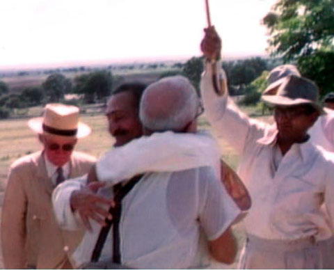 1954 - Meherabad, India : Meher Baba is hugging Ben Hayman, Will is wearing the light coloured hat and Kumar is holding the umbrella.