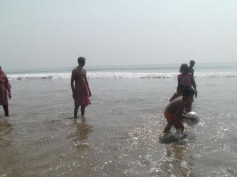 波打ち際で遊ぶインド人家族