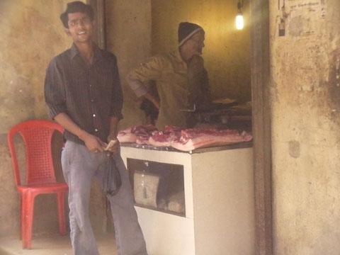 表通りで豚肉を売る店 手前の青年は買いに来た客だろうか