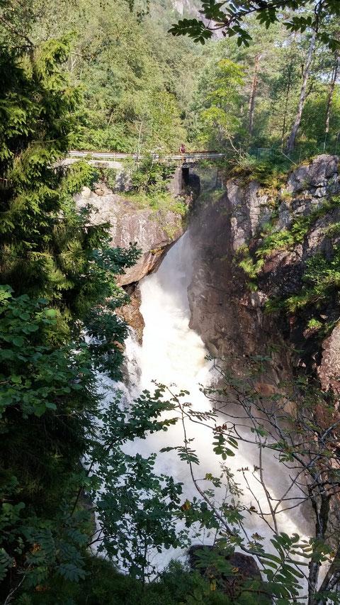 """Der Felsbrocken, der den Wasserfall teilt und auf dem die Brücke, die über den Wasserfall führt, aufgebaut ist, nennt man den Kvåsstein, """"Kvåsbolte"""" ."""