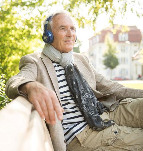 Älterer Herr geniesst entspannt Musik im Park
