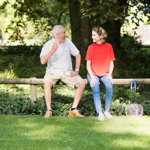 Un monsieur âgé raconte quelque chose à une jeune femme dans le parc