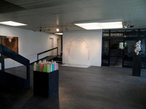 Blick in die Ausstellung – vorne die »kitchenqueens« von Anke Eilergerhard, links das Foto von Trudy Dahan, an der weißen Wand die Skulptur »shape« von Ev Pommer und ganz rechts »Denkmal« von Anke Eilergerhard.