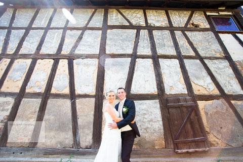 Hochzeitspaar vor einem Fachwerkhaus bei Nidderau-Heldenbergen fotografiert durch den Hochzeitsfotograf Haanu und Gelnhausen.