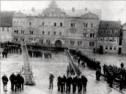 """Feuerwehrübung auf dem Roßmarkt Juli 1899 im Rahmen des 16. unterfränkischen Kreisfeuerwehrtages - dahinter das """"Bauschhaus"""""""