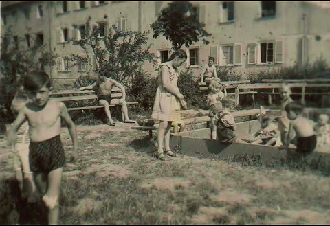 Kinder spielen - im Hintergrund Gebäude, in denen die Spuren des Zweiten Weltkriegs zu sehen sind....