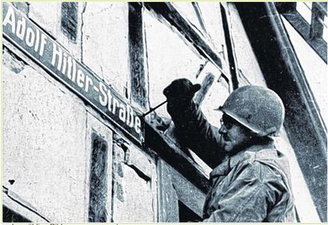 Das Straßenschild des Dritten Reiches wird von einem US-Soldaten entfernt - 1945