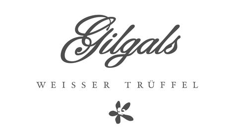Schriftzug Gilgals in geschwungener Schrift dunkelgrau auf weiß darunter der Zusatz weißer Trüffel darunter eine Blüte
