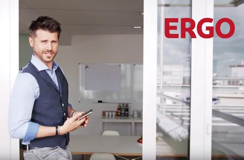 Moderator Thore Schölermann lehnt in einem Türrahmen eines Büros mit Smartphone in der Hand. Leistung: Producer für Erklärfilm. Für ERGO Versicherung. Ort: Hamburg