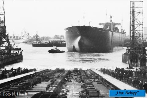 Die Schlepper bugsieren den Supertanker an die Werft-Pier.