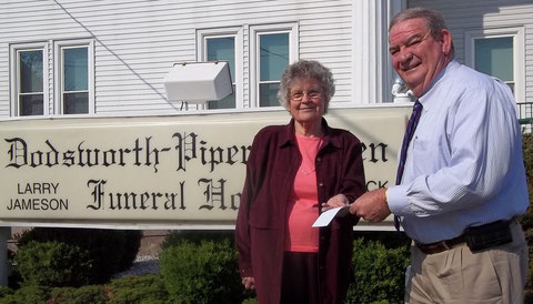 Gordana Rezab (left), president of the McDonough County Historical Society,  accepts a matching grant donation from Larry Jameson, representing Dodsworth-Piper-Wallen Funeral Home, to support the Cemetery Sign Project of the MCHS.