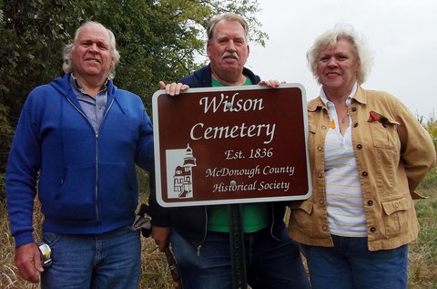 Richard Wilson (left), Ron Graham and his wife Marilyn Wilson Graham, accept a new sign marking the Wilson Cemetery provided by the McDonough County Historical Society.