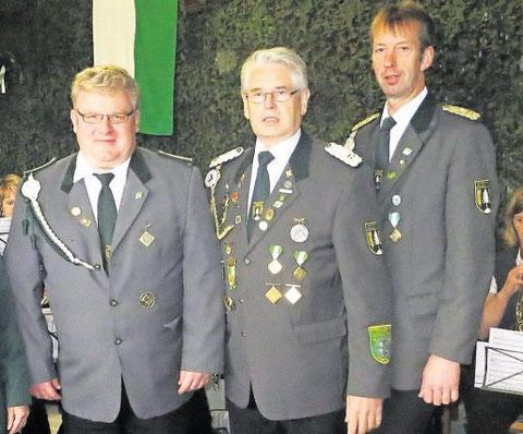 Schützenpräsident Detlef Brandt (r.) und Verbandsgeschäftsführer Gerd Brokelmann (M.) zeichneten Marco Kräling für uneigennützige Schützenarbeit aus. Foto: Brandt