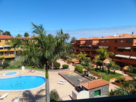 Blick von der Terrasse auf den Gemeinschaftspool und den subtropischen Garten der Wohnanlage.