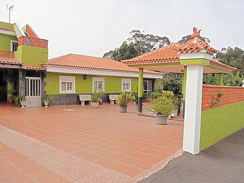 Eingangsbereich vom ebenerdigen Landhaus welches in Naturgrün gestrichen ist.