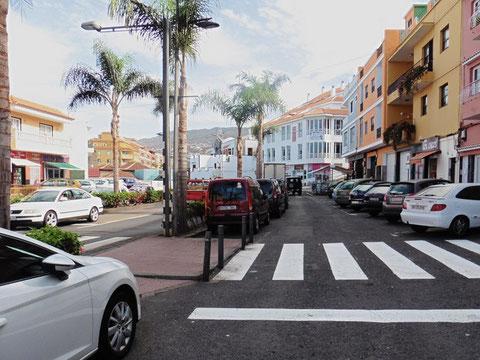 Belebte Einkaufsstraße mit Palmen.