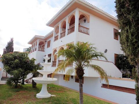 Blick auf die 3 stöckige Villa mit Palmen und subtropischen Bäumen vor dem Haus in Santa Cruz.
