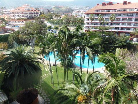 Hinter subtropischen Pflanzen der Gartenanlage sieht man den Pool und am Horizont den Teide.