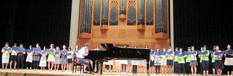 中1の教科書に載っていて、中学生なら誰もが知っている《マイ バラード》も松井孝夫先生の作品。2010年8月1日、オープンキャンパス・オープニングセレモニーで、千名を超える来場者を前に、松井先生自身のピアノ、音楽学部の学生の合唱で披露された。(撮影:山本)