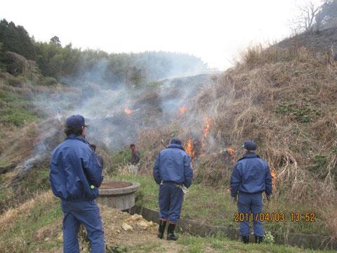 皆で作業中。青い作業服の消防団が見守る。時には火点けも手伝う。