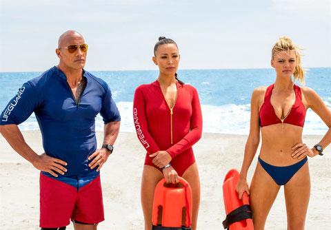 En rouge ou en bleu, une ou deux-pièces, short ou maillot de bain: les vêtements de travail des nageurs-sauveteurs (Dwayne Johnson, Ilfenesh Hadera, Kelly Rohrbach, de gauche à droite) sont variés (©Paramount Pictures).