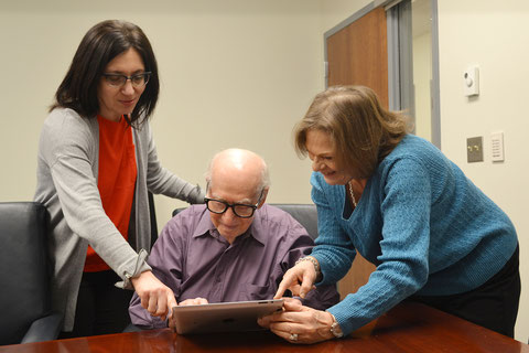 Ludmilla Goitman (left) and Eden Dine (right) help teach Moisey Mogilevsky, a local Holocaust Survivor, how to use his device during the Jewish Family Service Tablets & Technology program.