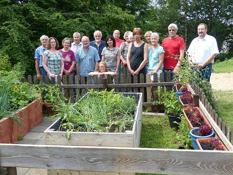 Workshopteilnehmer/Innen des NABU-KinderGartenpaten-Projekts 2014, die vom Umweltbeauftragten  der VG Westerburg Rolf Koch (r) herzlich begrüßt wurden, hinter dem erfolgreich bepflanzten Hochbeet der