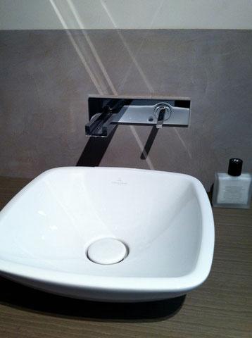 Une robinetterie murale et une vasque posée