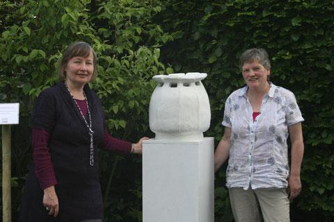 Nathalie Arun (links) und Cornelia Kalkhoff (rechts) mit der Mutterskulptur Hemerochorie in der Kleingartenanlage Münsterblick, Wienburgstraße 260 in Münster.